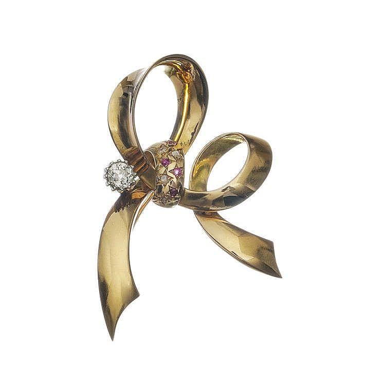 Broche nœud sertie d'un diamant taille ancienne (env. 0.5 ct) épaulant un motif pavé de rubis et de roses de diamant