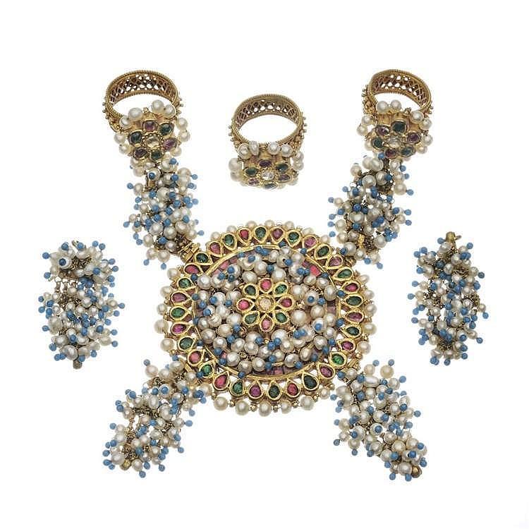 Parure de main composée de trois bagues, deux d'entre elles retenant un important motif rond serti d'un saphir blanc entouré de rubis et d'émeraudes en cabochon, de perles et de perles d'émail bleu. On joint une paire de boucles d'oreilles