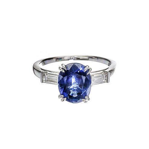 Bague sertie d'un saphir ovale (env. 3.3 ct) épaulé de deux diamants taille baguette