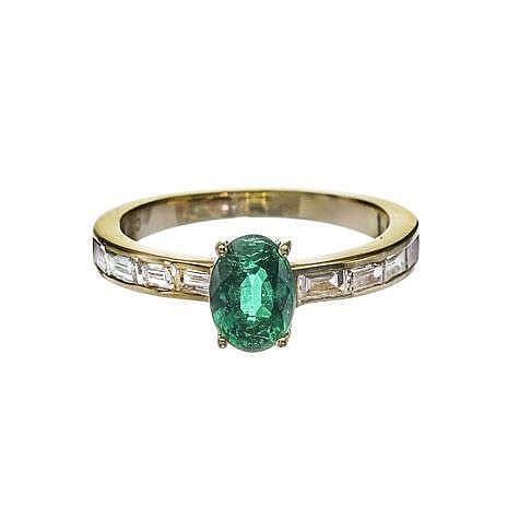 Bague sertie d'une émeraude taille ovale (env. 0.8 ct) sur un anneau semi-pavé de diamants taille baguette (env. 0.9 ct)