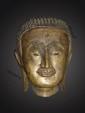Tête de Buddha à l'expression sereine les paupières mi closes préconisant le regard à l'intérieur de soi, la coiffure organisée en fines bouclettes hérissée, les oreilles aux lobbes allongés marque de sa noblesse. Bronze à traces de laque et de