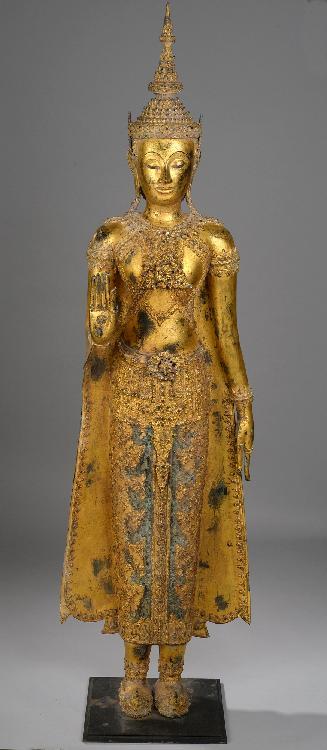 Important Bouddha paré et couronné, debout la main droite en abayamudra, geste du renoncement, la main gauche le long du pan déployé de sa robe monastique utarasanga richement ouvragé .Bronze laqué et doré. Royaume de Rattanakosin. Thaïlande. Fin 18