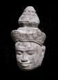 Tête de Vishnu couronnée d'un diadème rehaussé d'un tiare mukuta, le visage au sourire empreint de sérénité typiquement Khmer. Pierre grès gris. Khmer. Preah Ko. Cambodge. Fin du IX°S. 28cm. Importante érosion de la pierre. Petits éclats et manques.