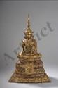 Buddha Maravijaya richement paré assis en virasana sur un haut socle pyramidale orné d'une bannière, la main droite en bumishparsha mudra et la gauche en dhynamudra, coiffé d'une haute tiare à ailettes. Bronze laqué et doré. Royaume de Ratanakosin.