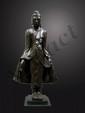 Bouddha debout dans une posture hiératique déployant de ses deux mains les pans de sa robe monastique, une main marquant la mudra de l'enseignement. Expression sereine du visage surmonté de la protubérance crânienne Ushnisha. Bronze à traces de