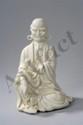 Lohan assis en délassement royale vêtu de sa robe monastique tenant un bol à offrandes. Porcelaine blanc de Chine de Dehua. Province du Fujuan. Chine. Début du 20iem siècle. Ht   25cm.
