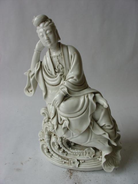 Le Boddhisattva Kwan Yin figuré assis en délassement royal sur une feuille de nénuphar, sa tête reposant sur sa main, vêtu d'une longue robe monastique. Porcelaine blanc de chine de Dehua. Province du Fujuan. Chine. Dynastie Qing. Début 20 ème