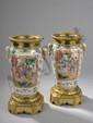 Paire de vases en porcelaine de Canton  décoré en émaux polychromes à montures piètement et col de bronze doré. Chine. Dynastie Qing. 19 ème siècle. H. 26,5 cm. Diam 13cm.