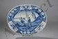 Plat ovale de la Compagnie des Indes en porcelaine blanche décoré en bleu cobalt sous couverte de personnages dans un jardin. Chine. Dynastie Qing. 18ème siècle. L 37,5cm.