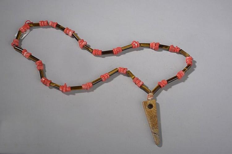 Collier ethnographique recomposé selon la tradition de perles d'aeil de tigre, corail terminé par une pendeloque triangulaire. Chine. Yunnan.