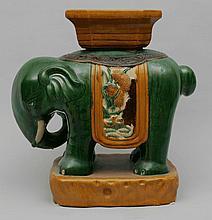Tabouret zoomorphe illustrant un éléphant harnaché. Céramique à glaçure verte et jaune dans l'esprit des Ming. Chine. Dynastie Qing. Fin 19 ème siècle. 57cmxlong36x29cm.