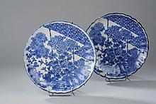 Paire de plats à marli polylobé en porcelaine blanche décorée en bleu de bouquets de chrysanthèmes , pivoines, passereaux en vol et motifs géométriques. Japon. Période Edo. 19 ème siècle.  Diam 28cm. Petit éclat à l'un.