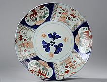 Plat en porcelaine imari à décor floral en réserve polylobé et frises géométriques. Japon. Période Meiji. 1868 à 1926. Diam 50cm.