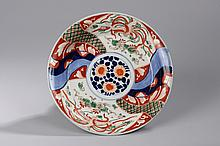 Plat creux en porcelaine imari du Japon décoré en réserve de motifs floraux et phaenix en vol. Japon. 19 ème siècle.  Diam 28cm.