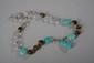 Collier recomposé selon la tradition de perles de turquoises, aeil de tigre et cristal de roche séparées par des bagues et perles de métal argenté terminé par une pendeloque. Tibet.