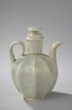 Verseuse Qinbaï couverte à corps godronné, anse de préhension et bec curviligne en fin grès porcelaineux à glaçure monochrome céladon bleuté translucide finement craquelé. Chine. Dynastie Yuan. 1279 à 1368. Ht   21cm. Diam au col   3,5cm.