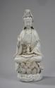 Kwan Yin assis en méditation sur un socle lotiforme faisant le geste de l'enseignement d'une main et de l'autre tenant le kalasha, vase d'immortalité. Porcelaine de Dehua dites blanc de Chine. Province du Fujuan. Chine. Dynastie Qing 32x14cm.