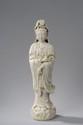 Kwan Yin, le Boddhisattva de la compassion figuré debout sur des flots bouillonnants vêtu de sa robe monastique tenant le rosaire et une offrande.  Porcelaine blanc de Chine de Dehua. Province du Fujuan. Chine. Dynastie Qing. 48cm.