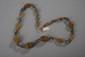 Collier recomposé selon la tradition de perles d'agate brune et miel de forme oblongue et godronnée et métal argenté. Inde du Nord.