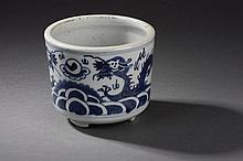 Brûle parfum cylindrique tripode en porcelaine blanche décoré en bleu cobalt sous couverte de deux dragons affrontés au dessus de flots bouillonnants. Chine. Dynastie Ming. 1368 à 1644. Ht  11cm x12,5cm.