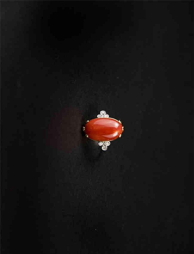 A coral and diamond ring, the oval coral in a claw setting, with brilliant cut diamonds to the shoulder珊瑚钻石戒指