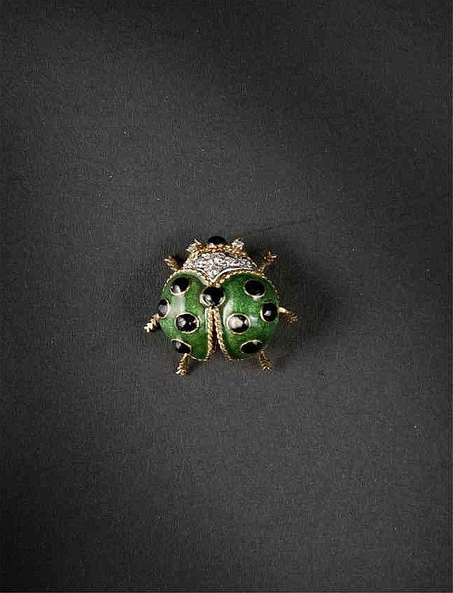 A gold and enamel ladybug brooch 18K gold with a green body and black dots, accented with eight full-cut diamonds, 1'' x 1 1/4'', 9.6 g gross