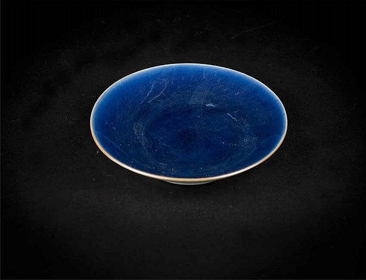 A blue gazed dish in monochrome blue on the inside and white on the reverse, potted with steep flaring sides, the rim in golden-brown; Jiaqing seal mark and of the period. 清嘉庆蓝釉描金画龙碟