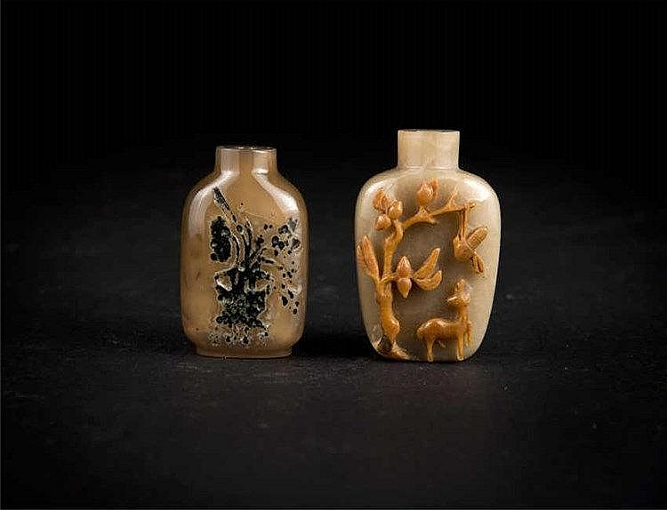 Two agate snuff bottles with carved designs against a brown ground; Qing dynasty. Provenance : Bonhams, London 清玉红皮雕树鹿鼻烟壶 玛瑙黑花草鼻烟壶