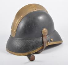 A late 19th/early 20th century fireman's brass mounted black leather helmet