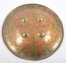 An antique Indian shield, Dhal, engraved brass with red and black enamellin
