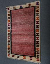 Gabbeh wool rug; with red speckled field, enclosed by cream borders,with H