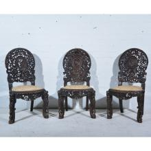Three Burmese carved hardwood side chairs, cartouche panel backs, upholster