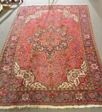 Persian carpet, central floral medallion on a crimson ground, with scrollin