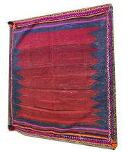 A Kilim style rug, maroon field against a navy ground, enclosed by vibrant
