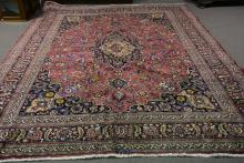 A Meshed carpet, central floral medallion against a burgundy ground with sc
