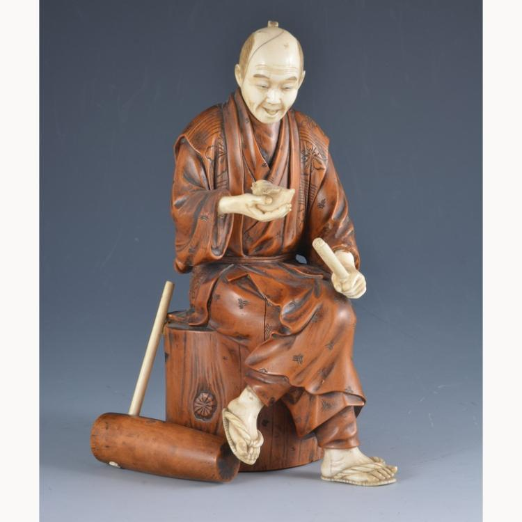 A japanese carved ivory and boxwood okimono seated man wi