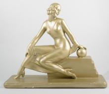 An Art Deco style figure of a lady, re-gilt finish, 36cm high, 44cm wide.