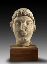 Limestone relief head of a young beardless man