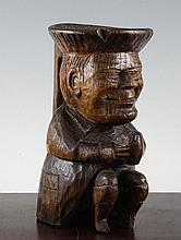An early 20th century carved oak treen model of a Toby jug, 8.5in.