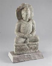 A Gandharan grey schist seated figure of Buddha, 2nd-4th century AD height 25.5cm