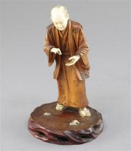 A Japanese ivory and boxwood okimono of a man, early 20th century, 17cm, losses