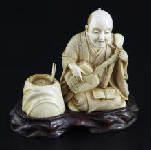 A Japanese ivory okimono of a kneeling musician, early 20th century, height 9.3cm, wood stand, damage to shamisen
