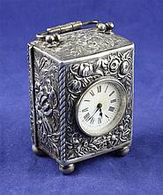 A late Victorian repousse silver cased miniature carriage timepiece, 3in.