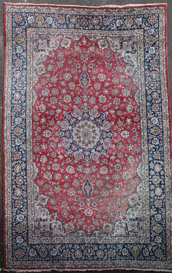 A large Isfahan red ground carpet, 14ft by 9ft 10in.