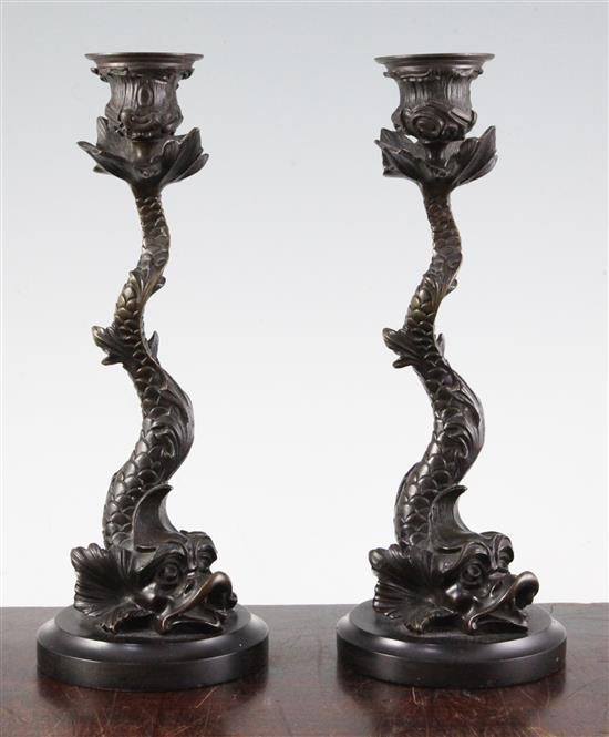A pair of 19th century bronze candlesticks, modelled as dolphins, 10.5in.