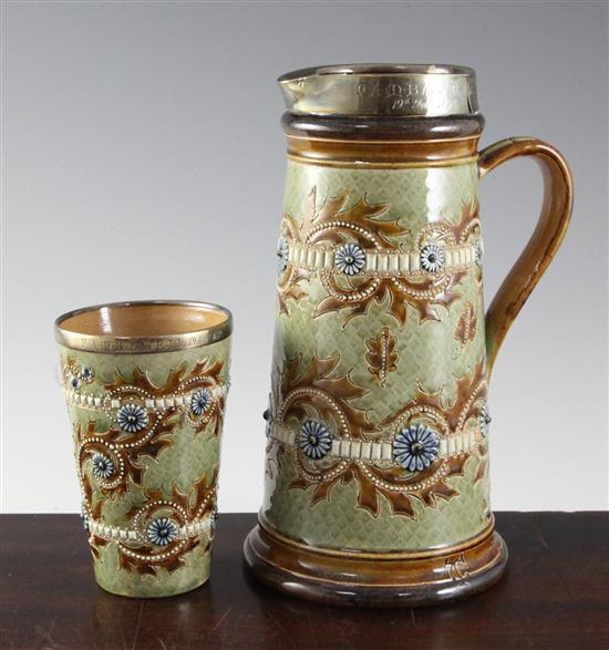 George Tinworth for Doulton Lambeth. A stoneware jug and matching beaker, 24.5cm (9.6in.) & 13cm (5.1in.)
