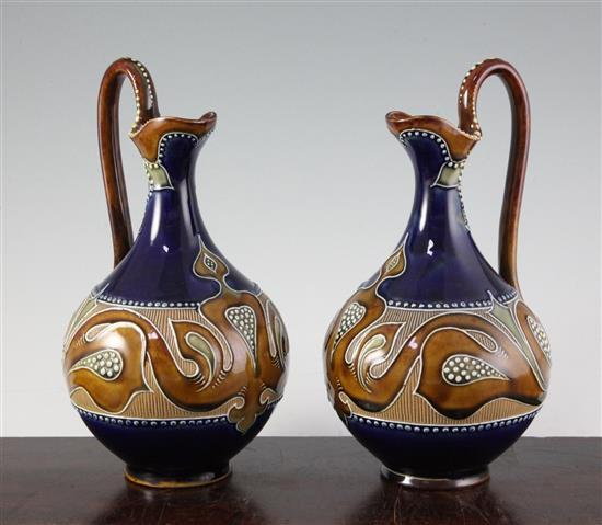 A pair of Doulton Lambeth Art Nouveau stoneware ewers, by Frank A Butler, c.1900, height 24cm (9.5in.)