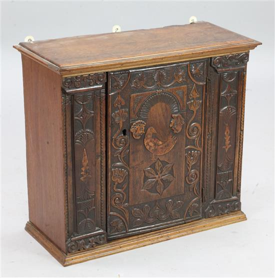 A 19th century Swiss carved walnut wall cupboard, W.2ft D.10in. H.1ft 10in.
