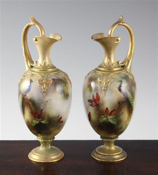 A pair of Royal Worcester peacock painted ewers, c.1905, 20.3cm (8in.), one restored