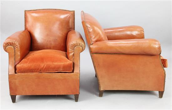 A pair of 1940's French russet leather club armchairs, W.2ft 7in. D.2ft 10in. H.2ft 8in.